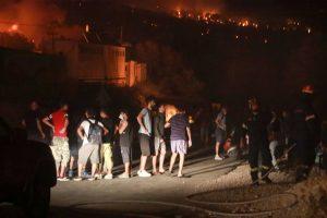 Refugiats veient l'incendi de Mória